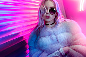 istock Teen hipster girl in stylish glasses and fur posing on street neon light wall background, female teenager fashion model woman with beautiful face looking at camera in city night light glow, back to 80s, portrait 1136418503