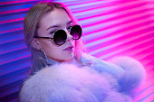 istock Teen hipster girl in stylish glasses and fur posing on street neon light wall background, female teenager fashion model woman with beautiful face looking at camera in city night light glow, back to 80s, portrait 1141918809