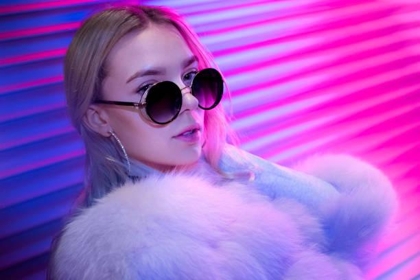スタイリッシュなメガネと毛皮でポーズのティーンヒップスターの女の子ストリートネオンライトウォールの背景、女性のティーンエイジャーファッションモデル女性美しい顔でカメラを見� - gen z ストックフォトと画像