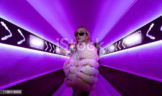 Teen hipster girl in stylish glasses and fur standing in purple neon lights elements on street wall, female teenager fashion model woman posing in city night violet bright club glow, back to 80s
