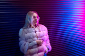istock Teen hipster girl in stylish glasses and fur standing on purple street neon light wall background, female teenager fashion model pretty young woman looking at night club city light glow, back to 80s 1138020166