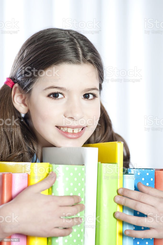 Teen hugging a lot of books. royalty-free stock photo