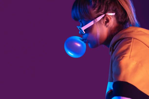 teen igen mädchen tragen stilvolle trendige sonnenbrille und hoodie blasen blase kaugummi profil seitenansicht, hübsche junge frau mode cooles modell mit bubblegum 80er jahre bei party lila studio-hintergrund, kopierraum - neon partylebensmittel stock-fotos und bilder
