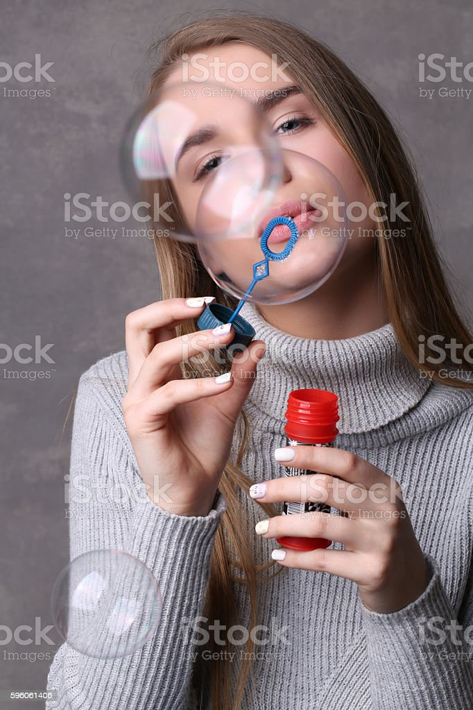 Teen in jersey blowing bubbles. Close up. Gray background royalty-free stock photo