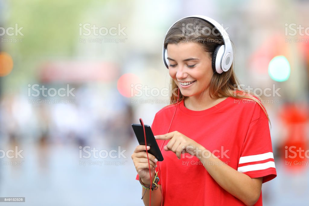 Teen in red listening to music on line on the street stock photo