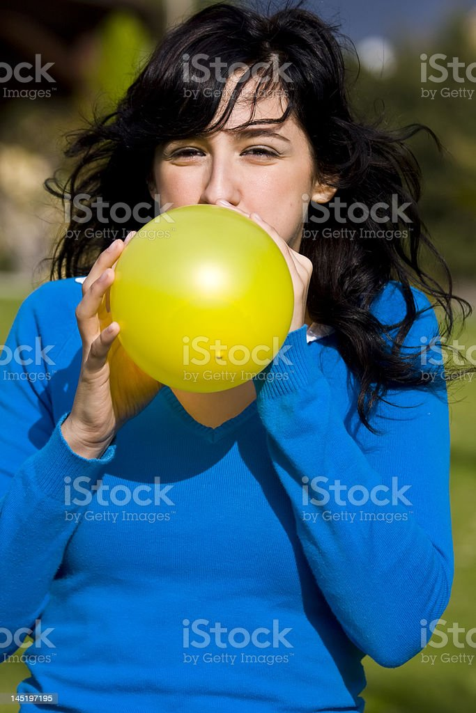 Teen inflating yellow balloon royalty-free stock photo