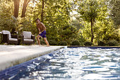 Teen jumping in pool