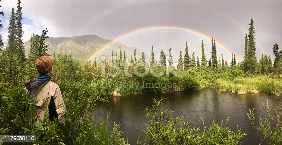 A red headed teen ager looks out over a beaver pond at a perfect double rainbow over the Nabesna Road in Wrangell St. Elias National Park. Alaska