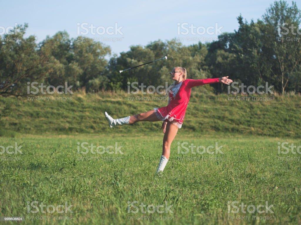 Chica adolescente Majorette girando el bastón al aire libre - foto de stock