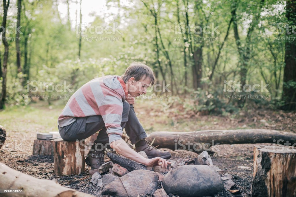 Teen man arranging stones of campfire at campsite. royalty-free stock photo