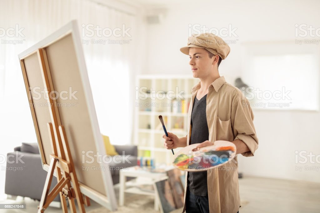 Teen painter looking at a canvas at home foto stock royalty-free