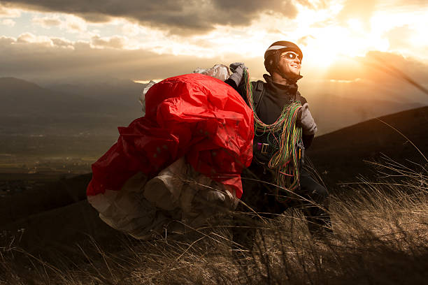 Teen paragliding Teen paragliding in mountain on sunset paragliding stock pictures, royalty-free photos & images