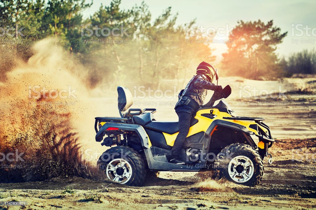 Teen riding ATV in sand dunes making a turn in the sand Cross-country quad bike race, extreme sports Adult Stock Photo