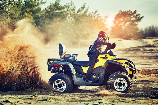 Teen Riding Atv In Sand Dunes Making A Turn In The Sand Stock Photo - Download Image Now