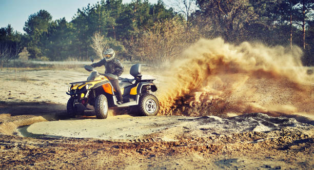 Teen riding ATV in sand dunes making a turn in the sand Cross-country quad bike race, extreme sports quadbike stock pictures, royalty-free photos & images