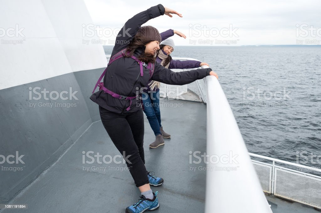 Teen Sisters Practicing Ballet on Ferry Deck, British Columbia, Canada stock photo
