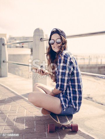 Retro style image of a teenage skater girl in hipster cap and sunglasses holding her phone and sitting on her skateboard on a paved walkway while smiling at the camera