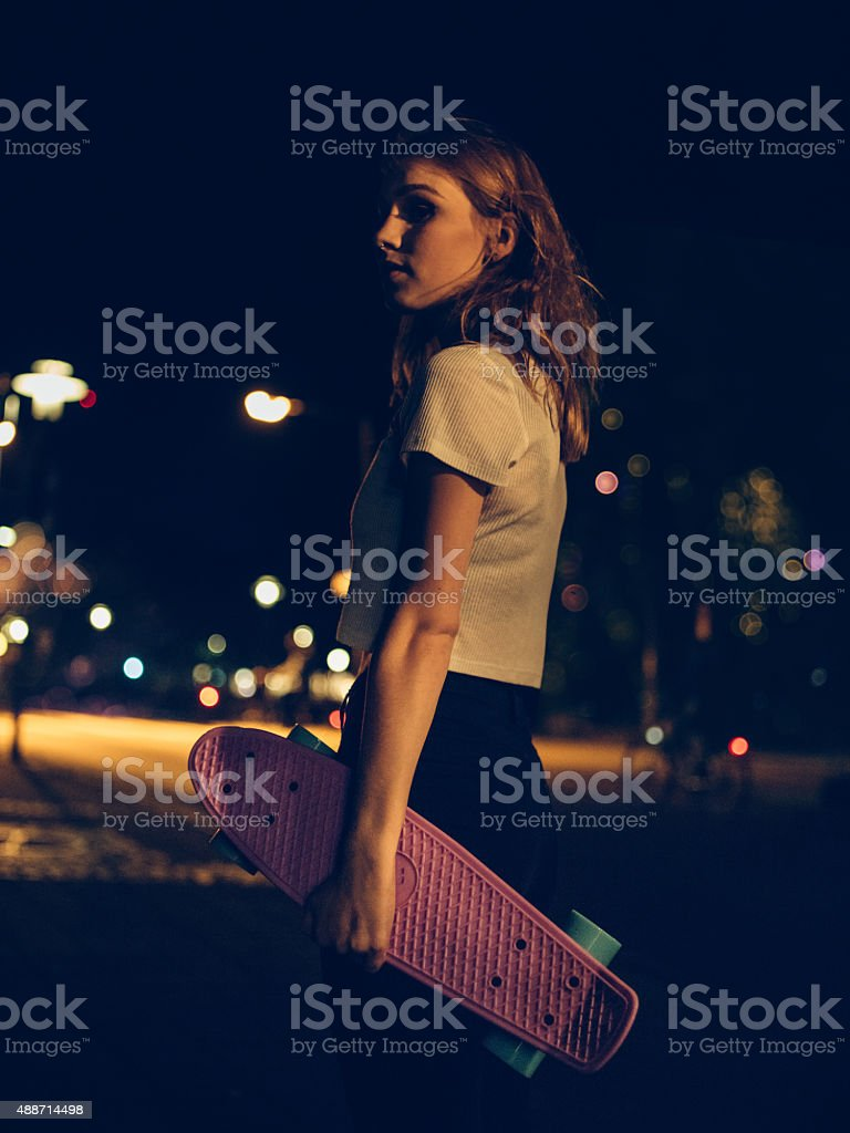 Teen skater girl standing on a city street at night Shadowy profile shot of a teenage skater girl holding her skateboard and standing alone at night on a city street 2015 Stock Photo