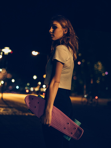 Teen Skater Girl Standing On A City Street At Night Stock Photo - Download Image Now