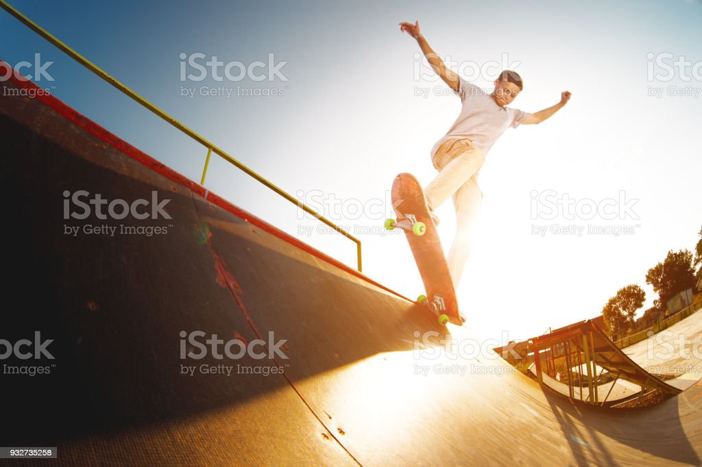 Teen skater hang up over a ramp on a skateboard in a skate park stock photo