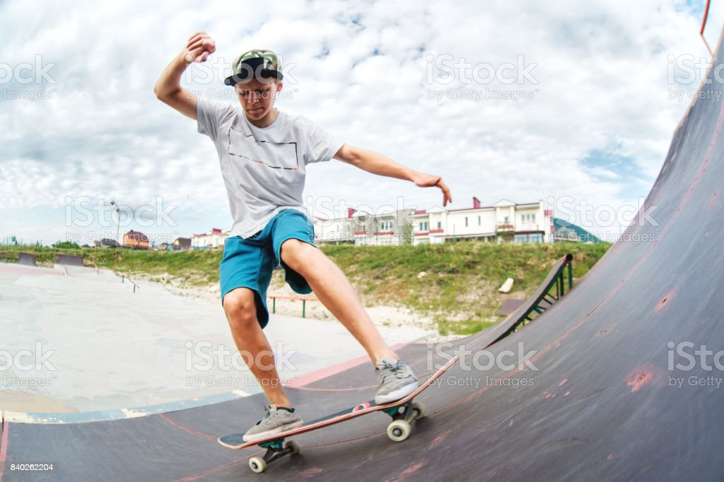 Teen skater rides over a ramp on a skateboard in a skate park stock photo