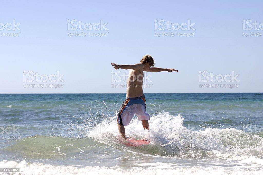 Teen skimboarding at the beach. royalty-free stock photo