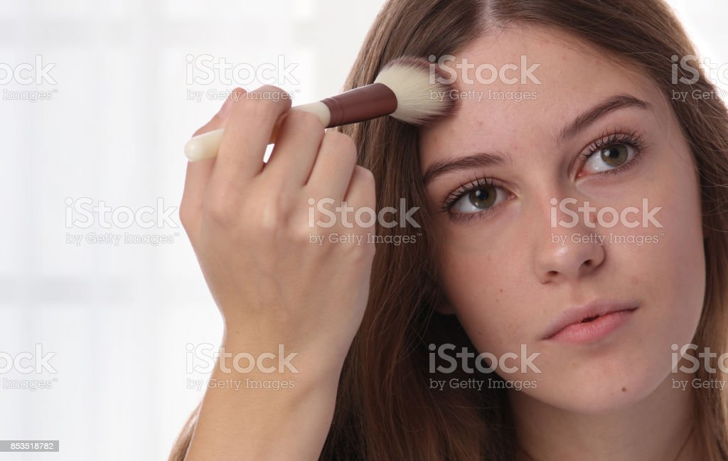 Teen Skin Problems : Young woman , teenage girl covering pimple and acne with powder foundation stock photo