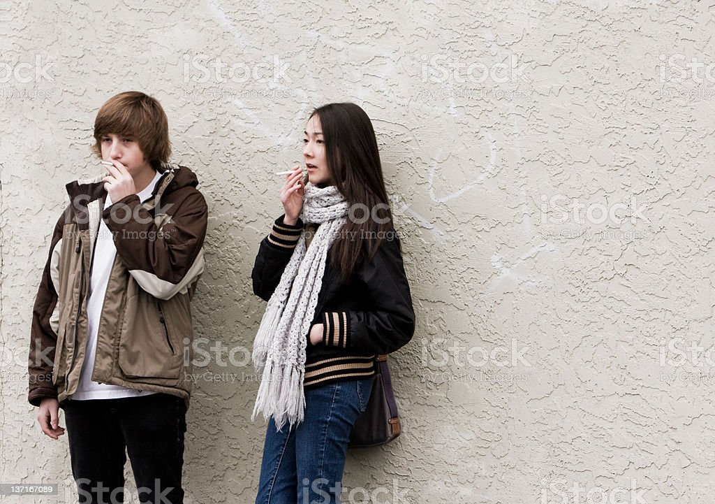 Teen Smokers Against Wall stock photo