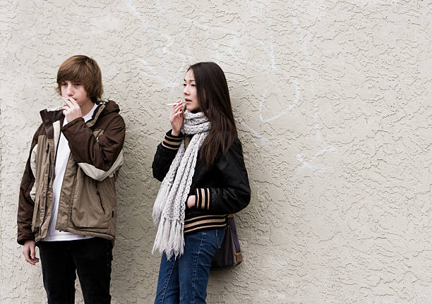 Teen Smokers Against Wall