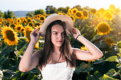 Girl in the blooming sunflowers on a brightly lit day. Having fun in nature.