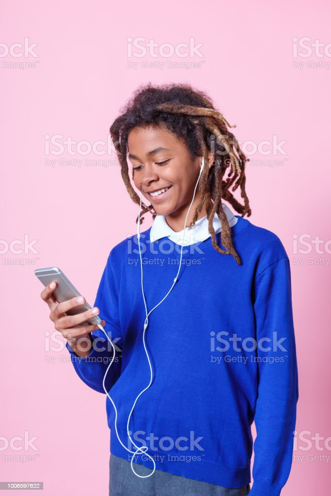 Teen student listening music with phone Teen student playing on mobile phone and listening to music with earphones. School boy with dreadlocks using mobile phone and listening music over pink background. 12-13 Years Stock Photo