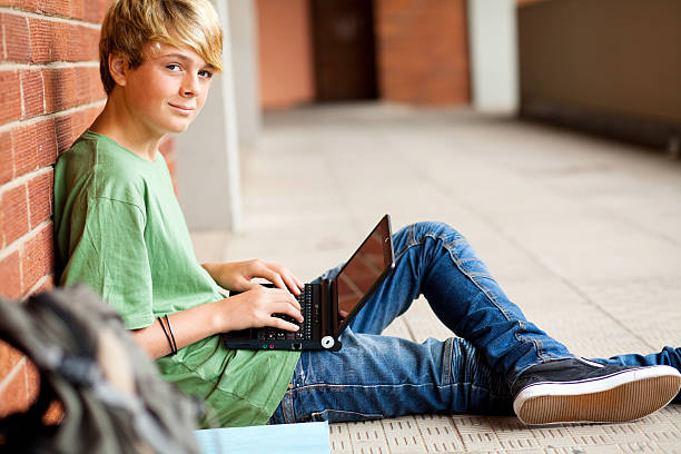 teen student using laptop in school stock photo