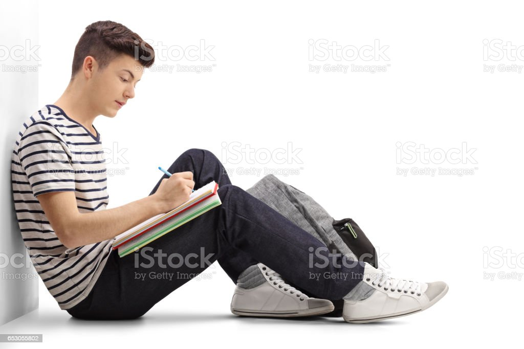Teen student writing in a notebook - Photo