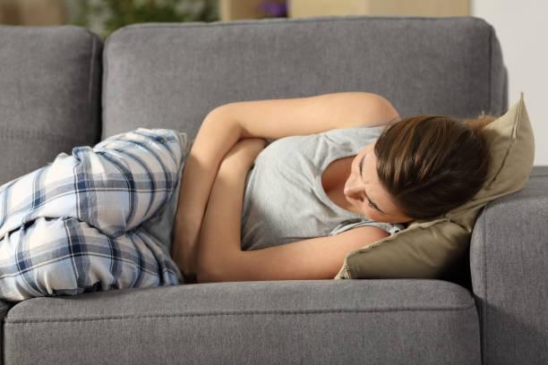 adolescente sofrendo sintomas de pms de barriga - sistema digestivo humano - fotografias e filmes do acervo