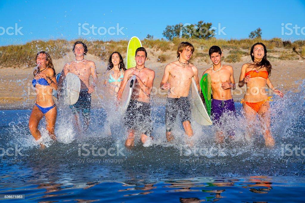 Teen surfers group running beach splashing - Stock image .