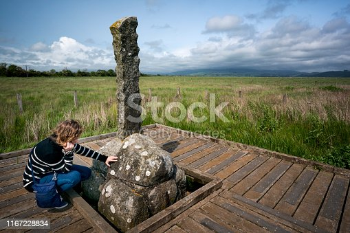 A teenage girl touches the rock on the wooden platform representing the Martyr's Stake memorializing two females (aged 18 and 63) drowned in the River Bladnoch when they refused to renounce their faith during Covenanter times in 1685, Wigtown, Scotland, UK, Europe