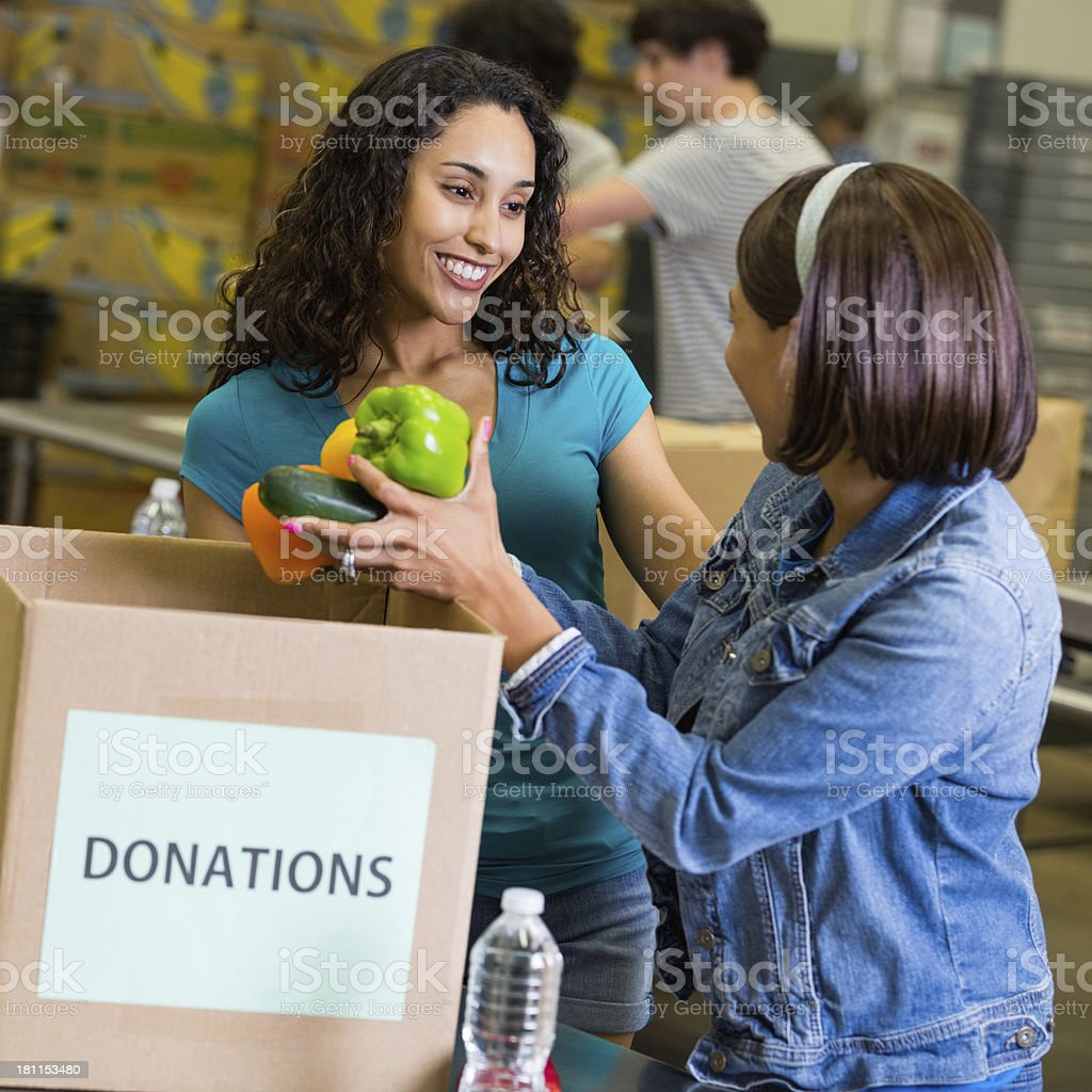 Teen volunteering at food donation center with friends royalty-free stock photo