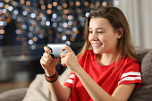 Teen watching media in a smart phone in the night