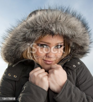 Pretty young woman wearing a winter jacket with sky in the background