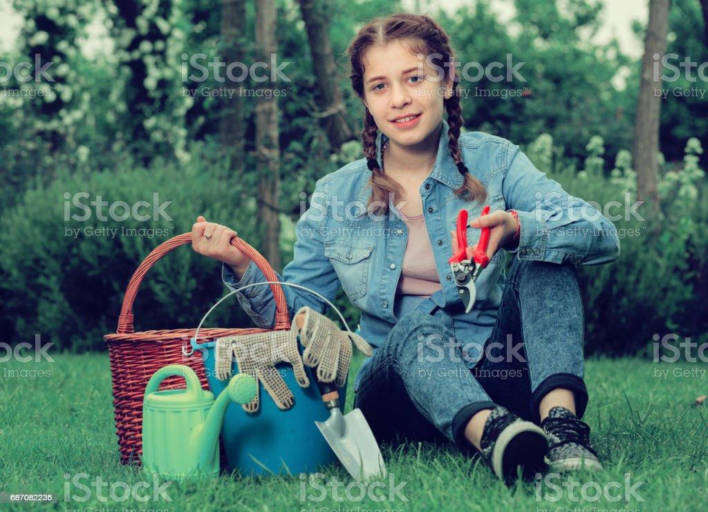 Teen mit Gartengeräten sitzen auf dem Rasen im Garten Lizenzfreies stock-foto
