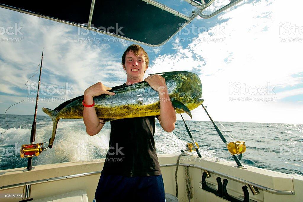 Teen with MahiMahi Dorado or Dolphin Fish on a boat stock photo