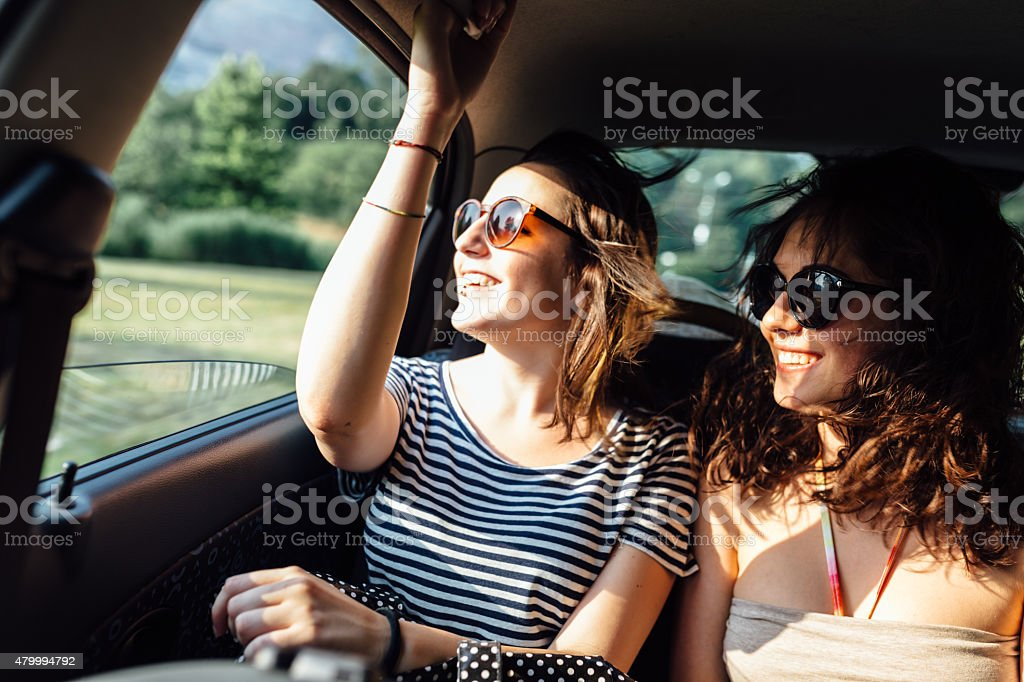 Teen woman friends traveling by car in the summer stock photo