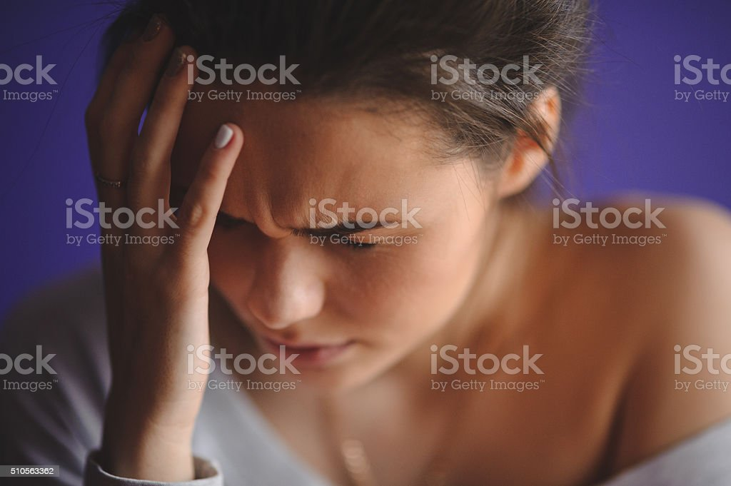 Teen woman with headache holding her hand to head stock photo