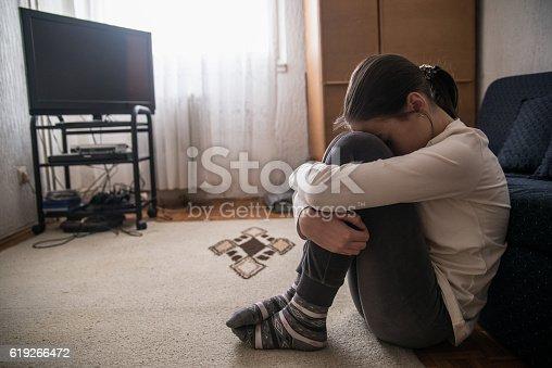 istock Teen woman with headache holding her head 619266472