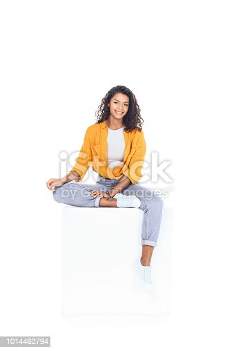 teenage african american student girl sitting on white cube and looking at camera isolated on white