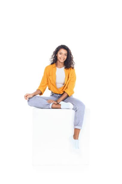 Teenager afroamerikanische Studentin sitzt auf weißen Würfel und Blick in die Kamera, die isoliert auf weiss – Foto