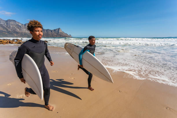 Teenage African Friends Going for a Surf Together stock photo
