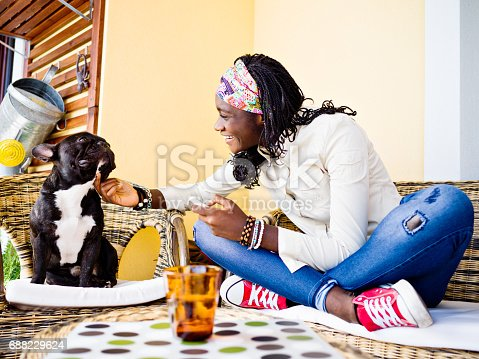 Teenage African girl with French Bulldog on balcony