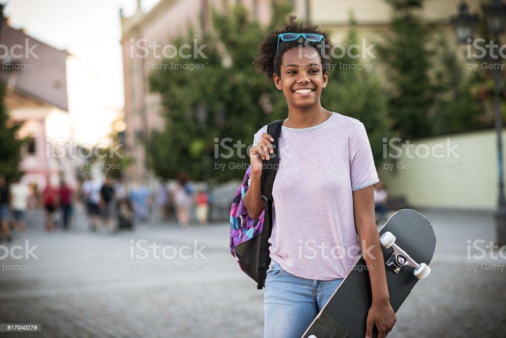 Afrikanischen Mädchens mit Skateboard und Rucksack zur Schule zu gehen. – Foto