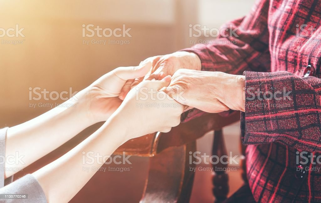 Teenage asia young girl carer holding grandma hands, concept of helping care for the elderly life with dark background, close up, copy space, cropped view Teenage asia young girl carer holding grandma hands, concept of helping care for the elderly life with dark background, close up, copy space, cropped view A Helping Hand Stock Photo